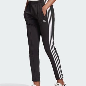 Black adidas trackpants, three strips